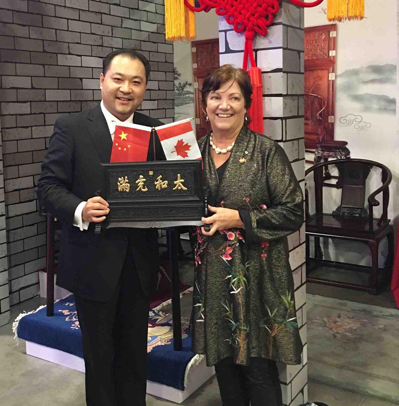"""关毅先生在加拿大首都渥太华向加拿大前副总理希拉·科普斯女士赠送""""太和充满""""牌匾"""