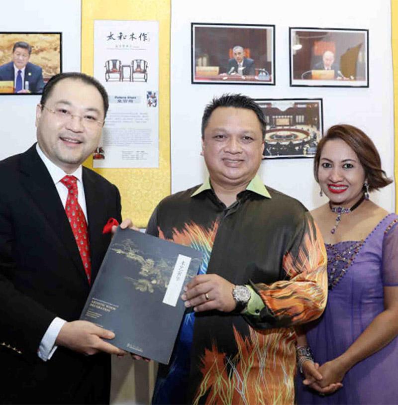 关毅先生(左)向马来西亚皇储端姑赛法依祖丁殿下、皇储妃莎卡丽殿下赠送故宫修复家具著作《木艺奢华》